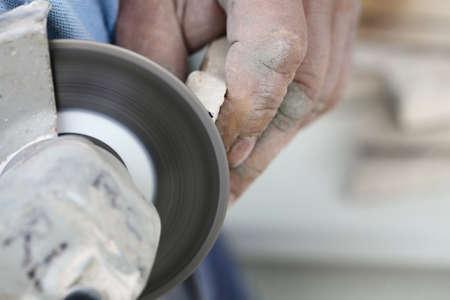 clinker tile: Renovaci�n en el hogar trabajador recortes de azulejo con amoladora angular hombre de la herramienta el�ctrica es suelo de baldosas en el sitio de la construcci�n de viviendas