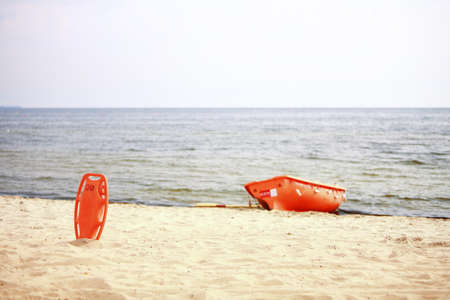 Beach life-saving. Lifeguard rescue equipment orange preserver tool and boat, red plastic buoyancy aid in the sand Stock Photo - 22338432