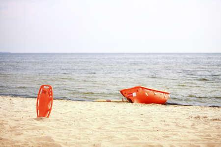 buoyancy: Salvavidas Beach. Salvavidas equipo herramienta preservador naranja rescate y bote de pl�stico ayuda a la flotabilidad roja en la arena Foto de archivo