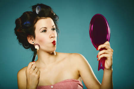 young woman preparing to party having fun, girl styling hair with curlers looking in the mirror applying make up retro style blue background photo