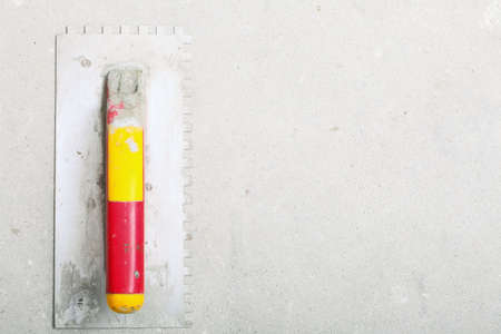 construction equipment dirty red yellow trowel used for masonry on rough unfinished concrete surface with copy space photo