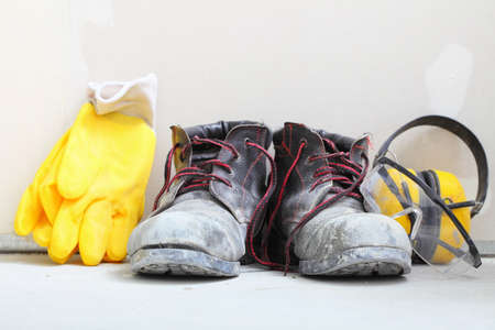 Renovation at home. Construction equipment tools work boots yellow protective noise muffs gloves in building site. photo