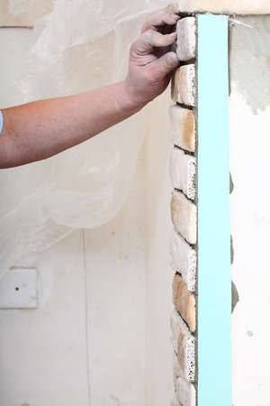 Renovation at home worker installing tiles brick on a wall construction site photo