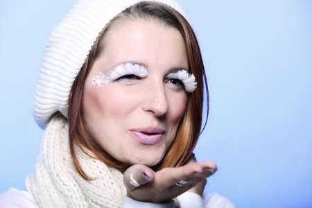 love blow: winter fashion beautiful woman in warm clothing stylish creative make up false long white eye lashes blowing a kiss blue background