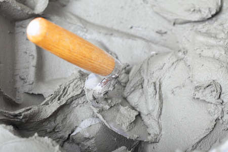 Renovation at home close up dirty trowel and bucket with mortar on construction building site Stock Photo - 22362652