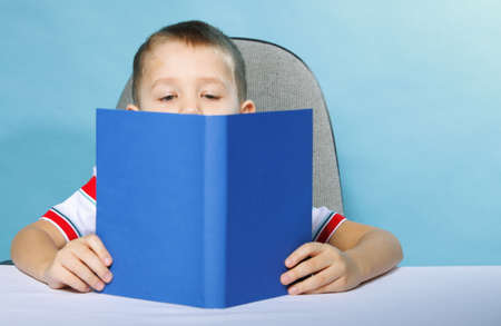 Young boy reading a book, child kid on blue background\ holding an open book