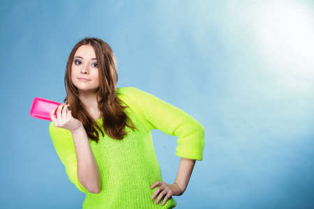 Happy girl young woman with mobile phone smartphone in pink cover studio shot blue background photo