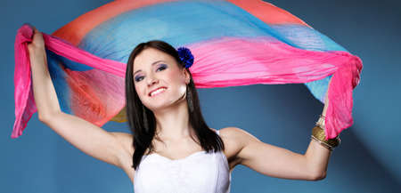 Pretty summer woman with multicolored flying shawl on blue background. Fashion photo photo