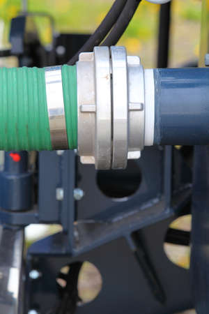green plastic hose tube is connected to a blue steel pipeline industrial detail photo
