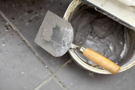 Renovation at home dirty trowel and bucket with mortar on construction building site Stock Photo - 22396934