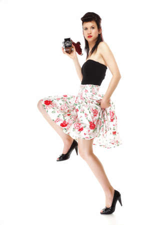 Full length pretty retro summer girl taking picture using vintage camera white background photo