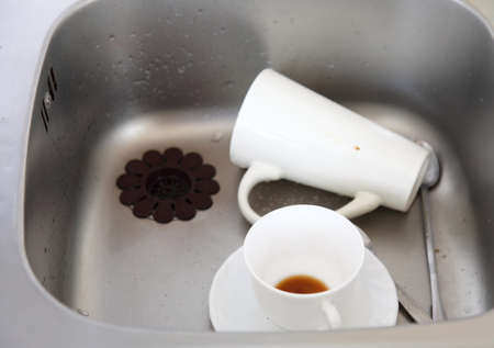 washup: Washing up. White coffee cups in the kitchen sink.