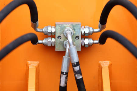 Multiple Black Hydraulic Hoses on an Excavator Orange Industrial Detail photo