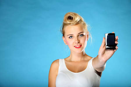 Technology . Happy pin up girl retro style offering mobile phone blue background photo
