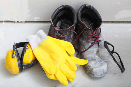 Renovation at home. Construction equipment tools work boots yellow protective noise muffs gloves glasses in building site. photo