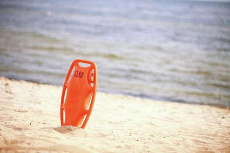 buoyancy: Beach herramienta de salvamento salvavidas rescate salvavidas equipo naranja, ayuda a la flotabilidad de pl�stico rojo en la arena Foto de archivo
