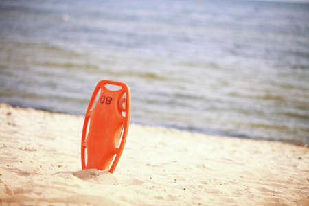 Beach life-saving  Lifeguard rescue equipment orange preserver tool, red plastic buoyancy aid in the sand photo