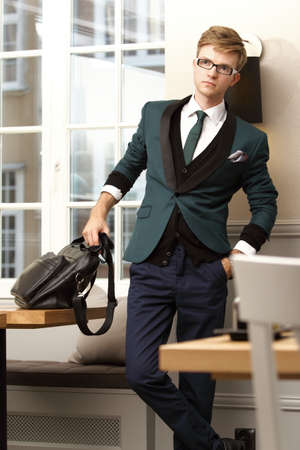 Young handsome stylish man fashion model posing in trendy cafe restaurant with bag photo