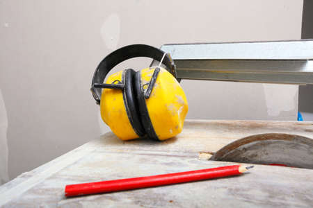Improvement renovation at home. Construction site work tools saw blades cutter to cut tile, protective headphones noise muffs photo