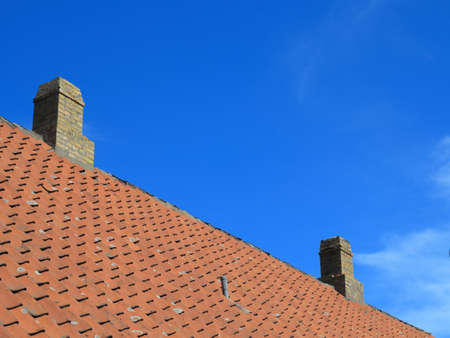 The old roofing tiles red clay house roof with chimney sky  photo