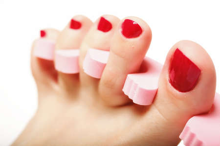 nail spa: foot pedicure applying womans feet with red toenails in toe separators white background