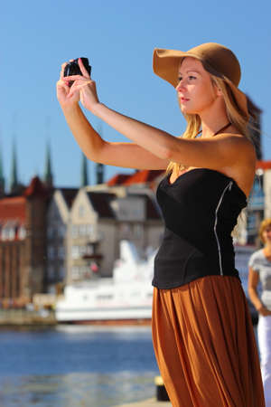 Female photographer. taking pictures. Stylish autumn traveler woman in hat with camera outdoors in european city, old town Gdansk in the background, Poland Europe photo