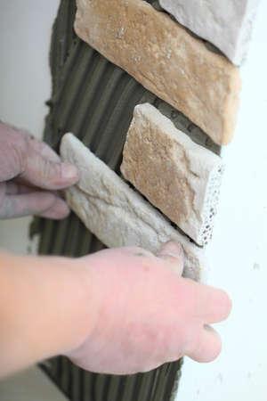 clinker tile: Renovaci�n de los trabajadores a domicilio instalar baldosas de clinker en un sitio de construcci�n de la pared Foto de archivo