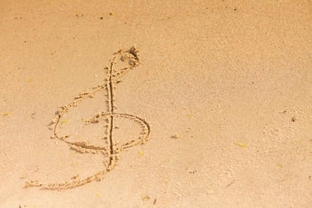orchestrate: Violin key treble clef drawn in sand outdoor