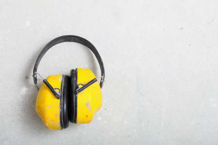 Ear hearing protection. Yellow working protective headphones noise muffs, toolwork in construction site photo