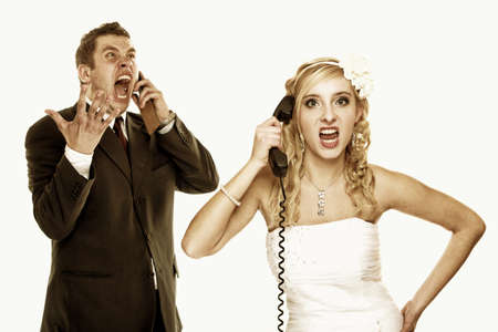 Wedding couple relationship difficulties. Angry woman man talking phone yelling at each other. Portrait fury bride groom. Isolated on white photo