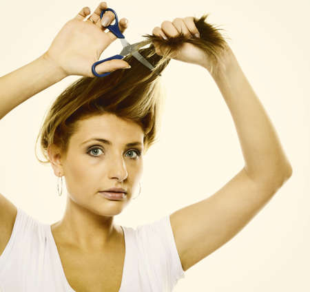 Damaged dry hair splitting ends. Young blonde woman cutting her hair with scissors - unhappy expression studoi shot photo
