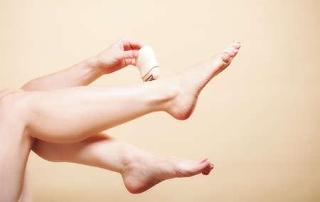 22665767 - Mujer afeitarse las piernas con maquinilla eléctrica de afeitar  depilación en naranja. La bella y la piel concepto de cuidado del cuerpo. 4521f8b2d947