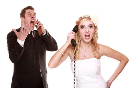 Wedding couple relationship difficulties. Angry woman man talking phone yelling at each other. Portrait fury bride groom. Isolated on white Stock Photo - 22685654
