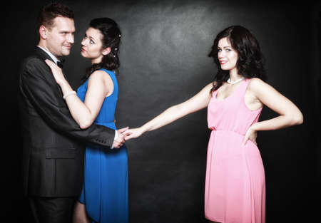 marital infidelity concept. Love triangle two women one man passion of love hate. Mistress betrayal within the family. Black background photo