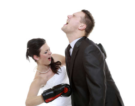 Bad relationship. Funny wedding couple expressive fighting. Woman showing her husband whos boss. Angry wife boxing husband. Isolated on white