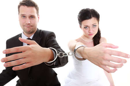 Break up ending relationship between husband and wife. Couple in divorce crisis. Man woman unhappy holding hands in handcuffs. Isolated photo
