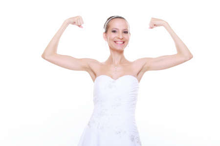 woman bride in wedding dress shows her muscles flexing biceps clenching fist isolated on white strength and power concept photo