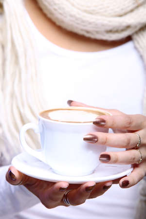 Closeup female hands holding a cup of latte coffee cappuccino hot drink in winter time blue background photo