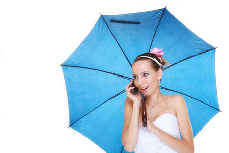 Wedding day at a raining day. Young romantic bride with blue umbrella talking phone isolated on white background