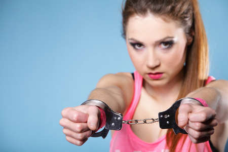 juvenile delinquent: teen crime - teenager girl in handcuffs studio shot