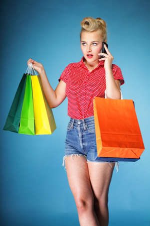 Retro style. Young woman in red dotted shirt and shorts with colourful shopping bags talking on cell phone Stock Photo - 22768409