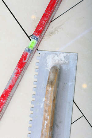 notched: construction equipment dirty notched trowel and level on new tile floor surface, tile floor adhesive Stock Photo
