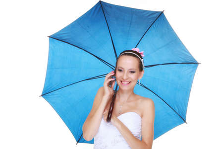 Wedding day at a raining day. Young romantic bride with blue umbrella talking phone  photo