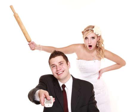 Wedding couple having argument - conflict, bad relationships. Angry woman fury bride yells at groom, her joyful husband watching TV. Isolated on white photo