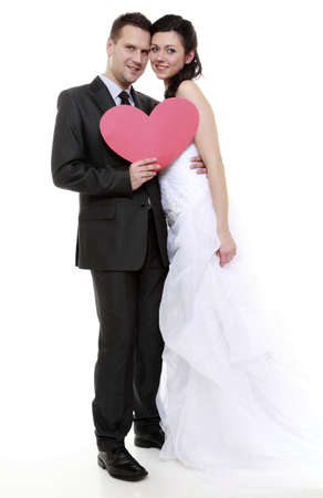 Wedding day. Full length happy bride and groom holding red heart   photo