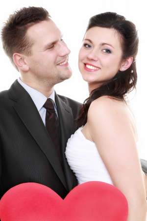 Wedding day. Portrait happy bride and groom holding red heart   photo