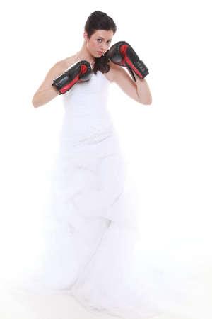 Emancipation idea concept. Bride in wedding dress wearing boxing gloves. Woman showing her power domination