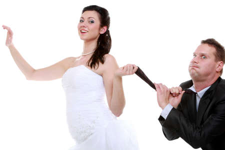 Emancipation idea concept. Humorous funny wedding couple bride and groom - woman pulling the tie of a man, trying to show her domination, isolated photo