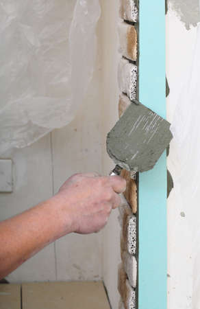clinker tile: Renovation at home worker installing tiles brick on a wall construction site