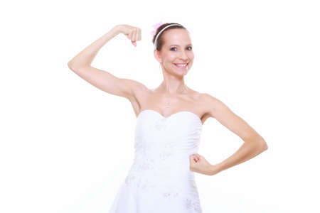 woman bride in wedding dress shows her muscles flexing biceps clenching fist isolated on white background strength and power concept photo